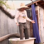 Rainwater harvester Brad Lancaster stands in his outdoor bathtub plumbed to water his fruit trees.
