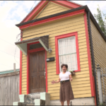 "Lillian stands in front of her 400-square-foot ""Shotgun cottage""."