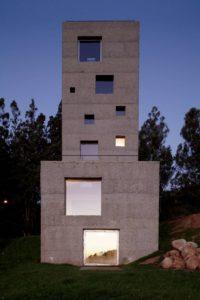El aspecto monolítico de la Casa-Cien parte del hormigón de su fachada y la disposición orgánica de ventanas en sus 7 plantas