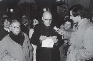 Michel Foucault (hablando ante el micrófono), acompañado por Jean-Paul Sartre (a la izquierda)
